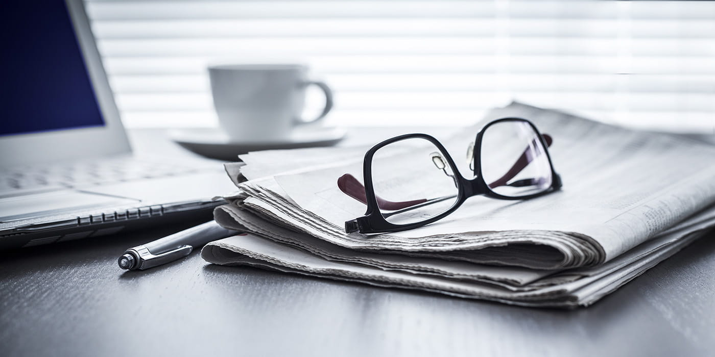 Reading glasses laying on top of a newspaper with a laptop and cup of coffee nearby