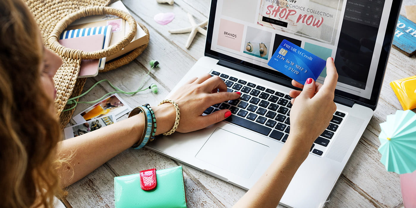 A person shopping online with their credit card in their hand