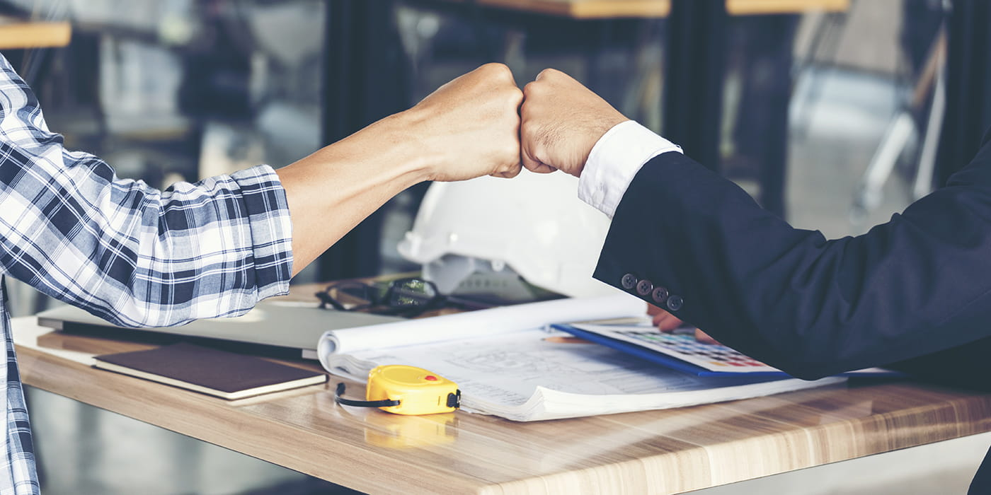 Two individuals fist bumping in a workplace
