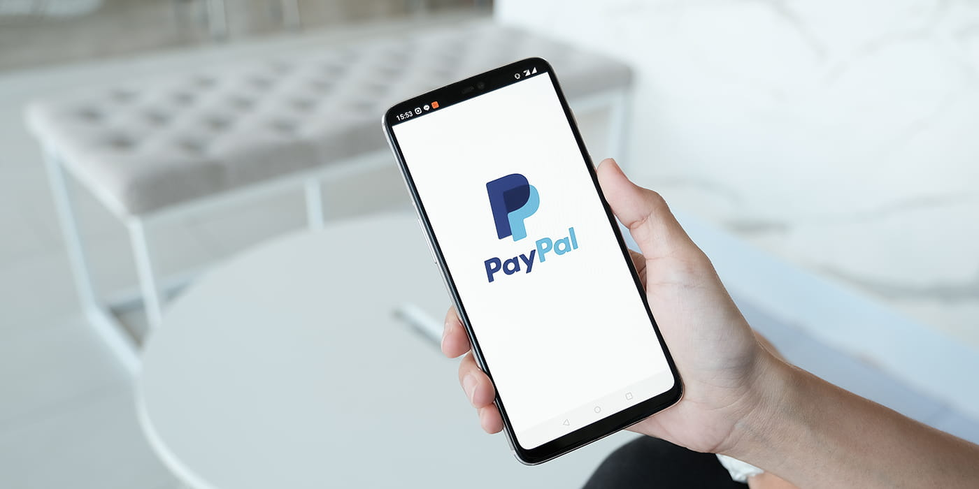 hand holding a phone with the paypal logo