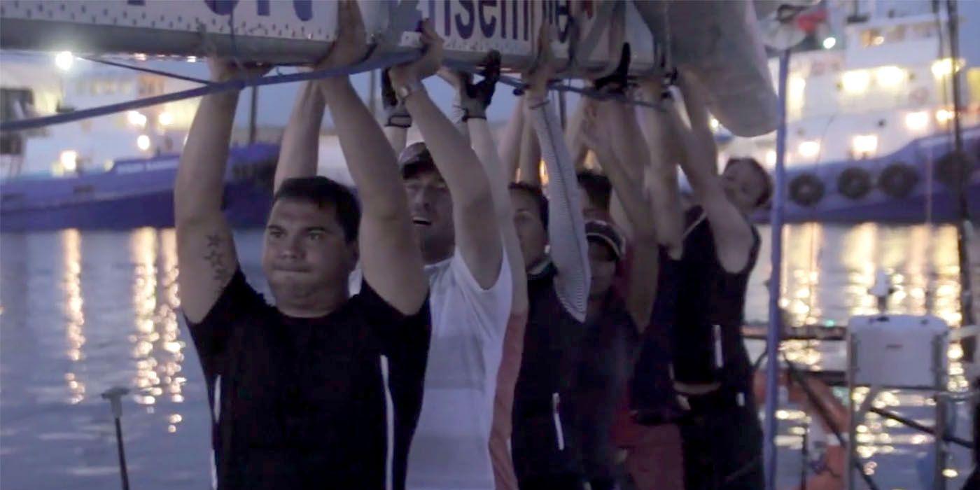 people lifting sailboat
