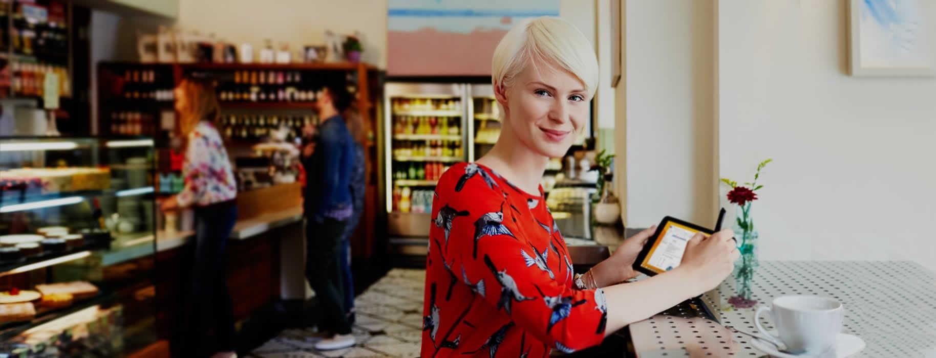 Señora en cafetería usando una tablet