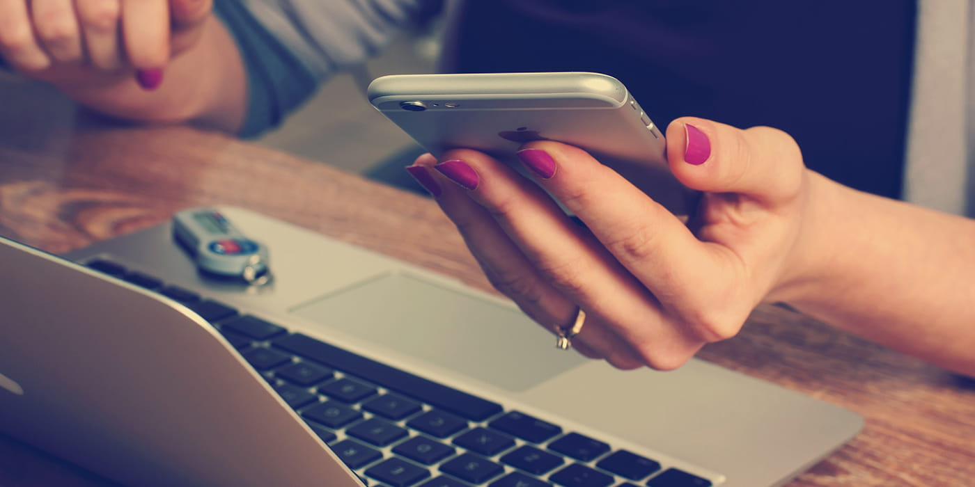 Woman with pink painted nails holding an iPhone sitting at a laptop