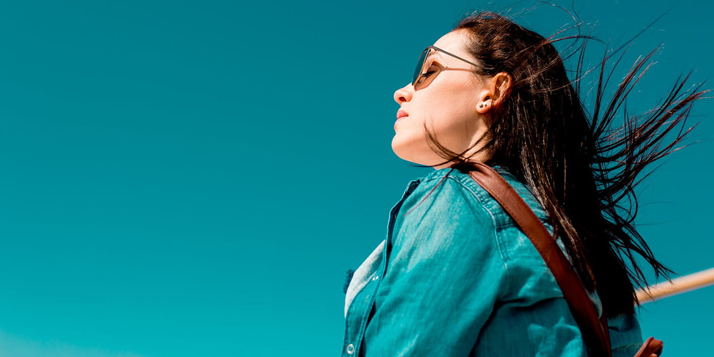 Woman wearing denim top and sunglasses with blue sky background