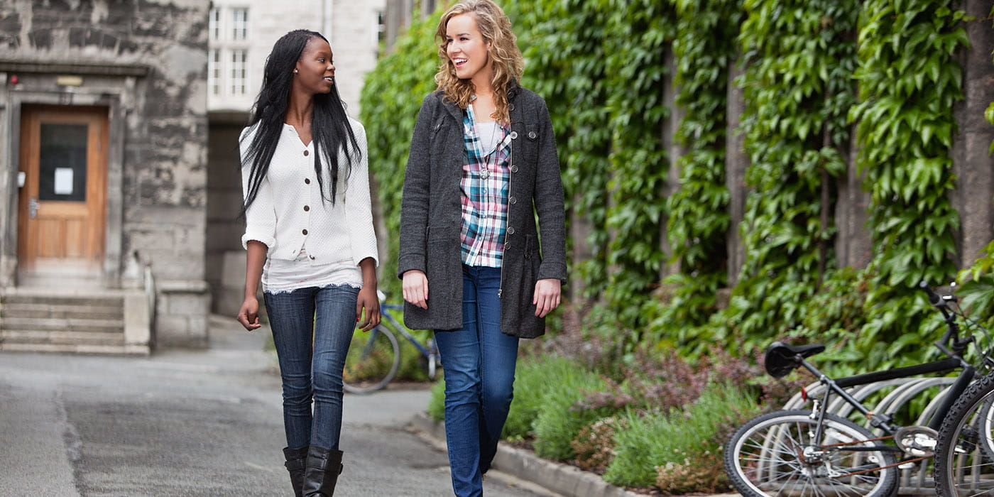 Two women conversing and walking down a street