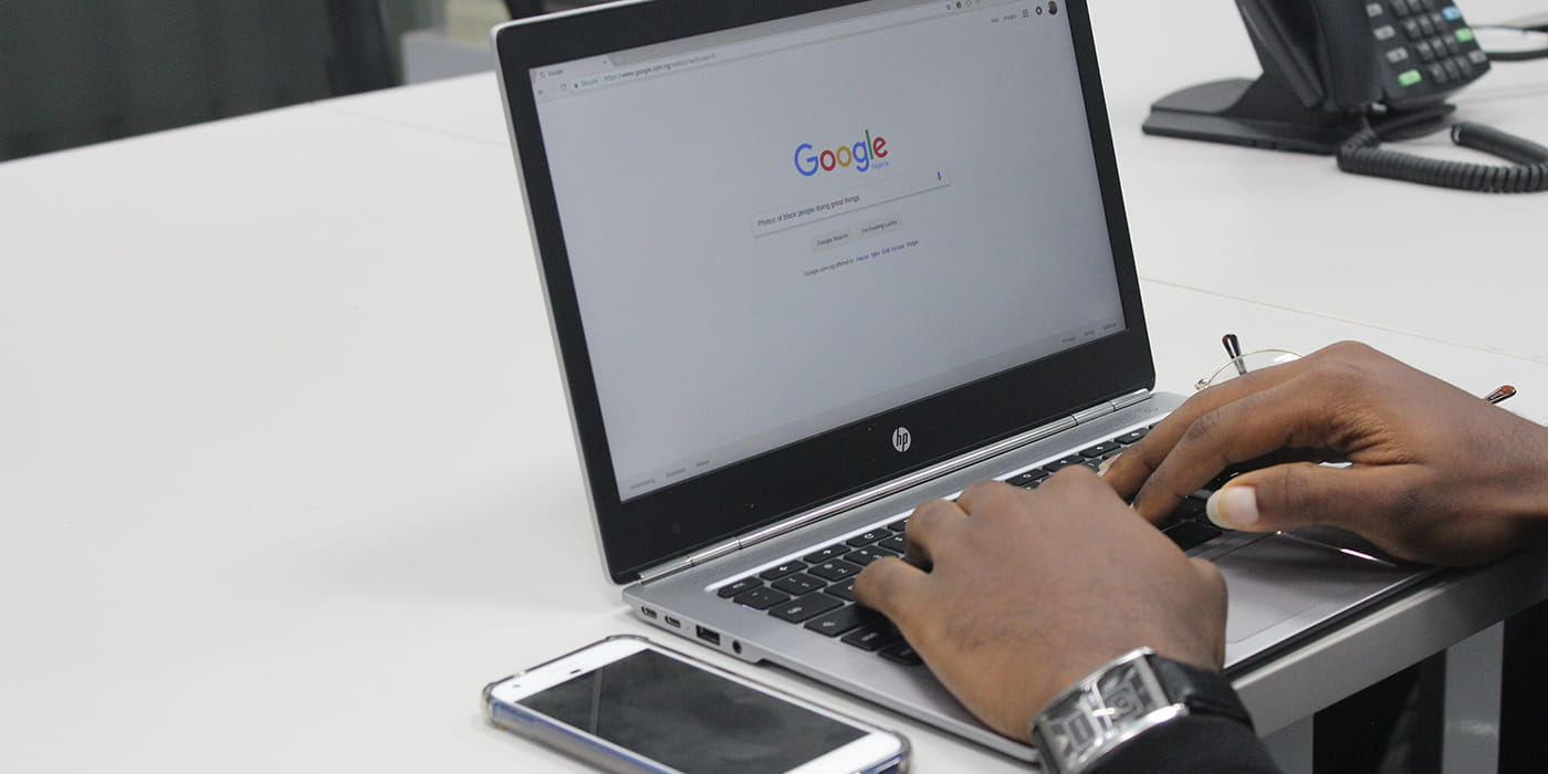 Hands using laptop to search on Google engine