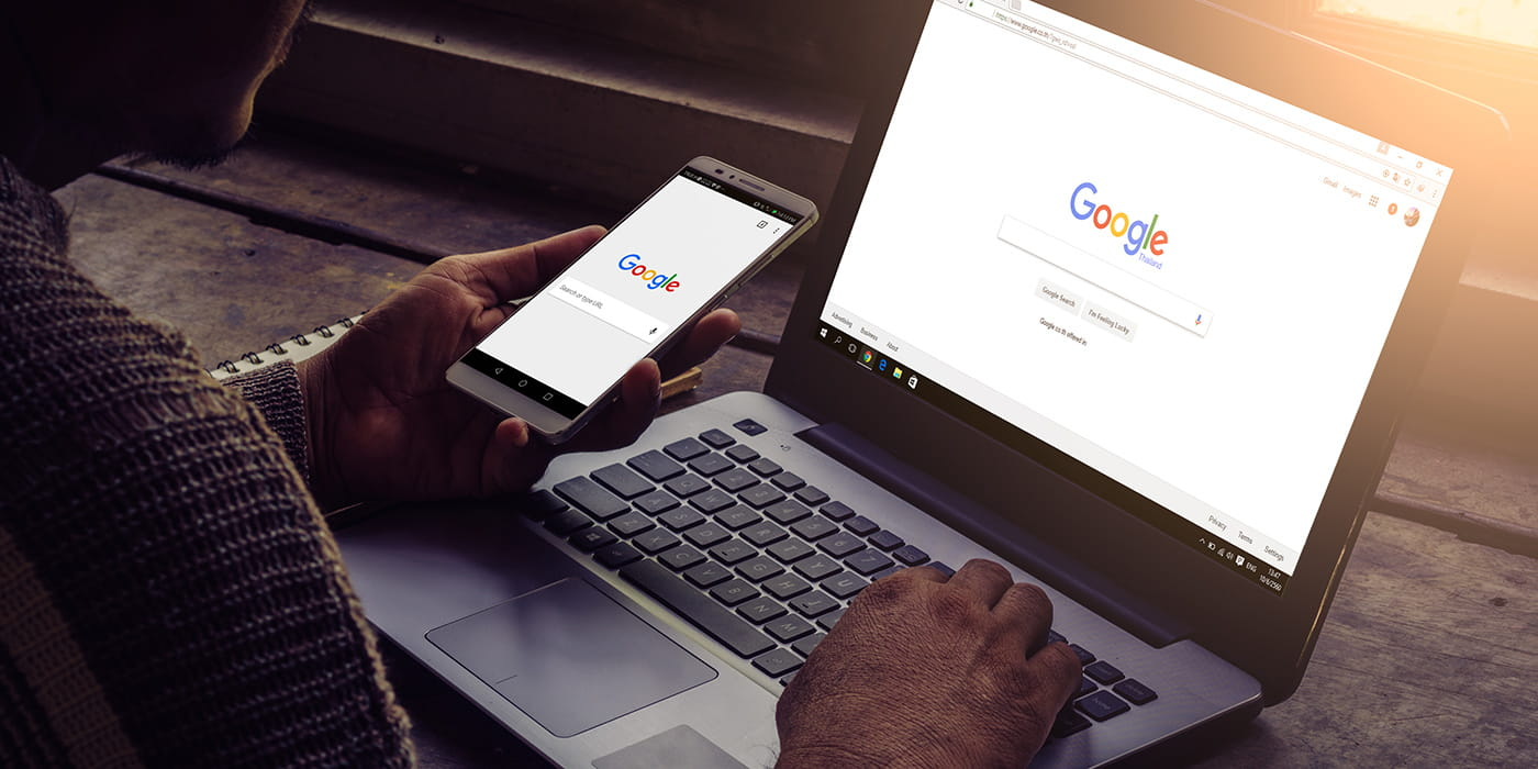 A laptop and phone showing the Google homescreen.