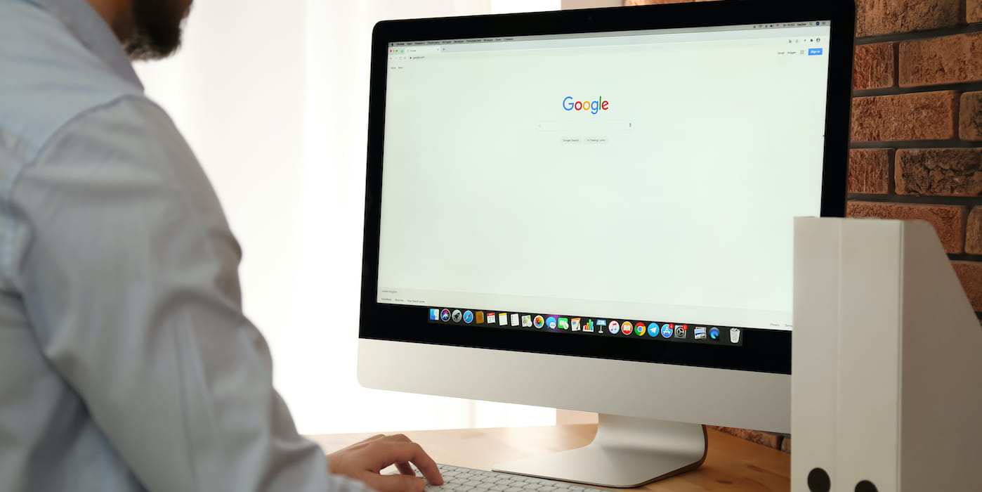 Man on computer with Google search on screen